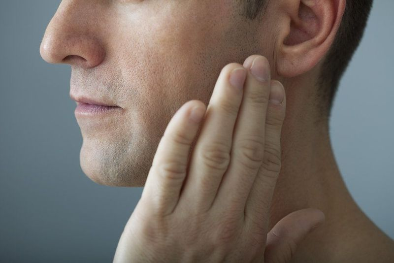 Male patient holding his painful jaw.